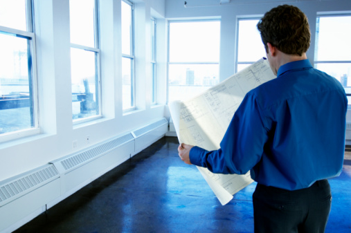 Man looking at blueprint in empty office, rear view