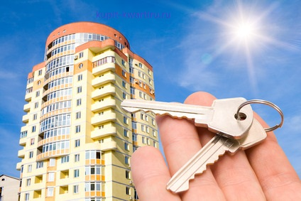 real estate concept. keys in fingers with building